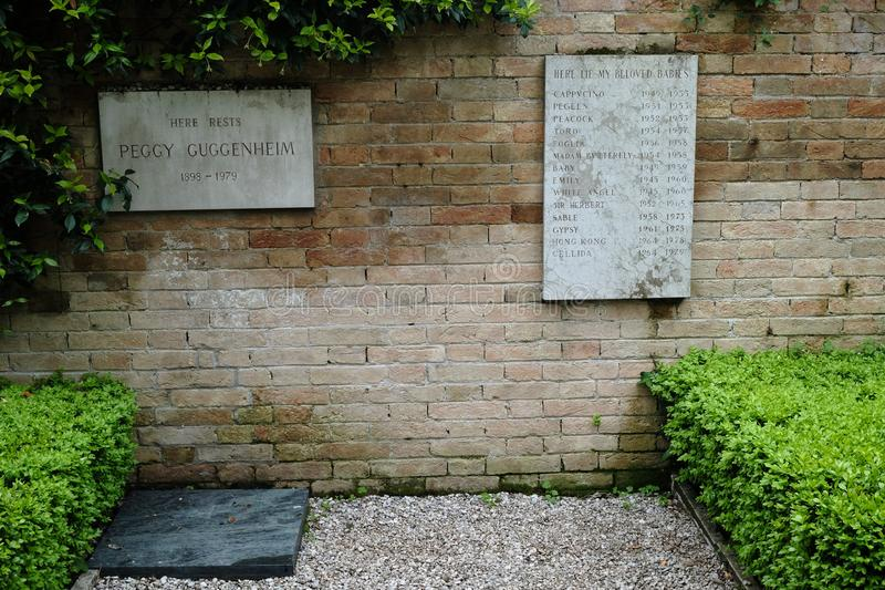 Venice, Italy, 05/03/2019 Grave of Peggy Guggenheim and a stone commemorating her pet dogs stock image