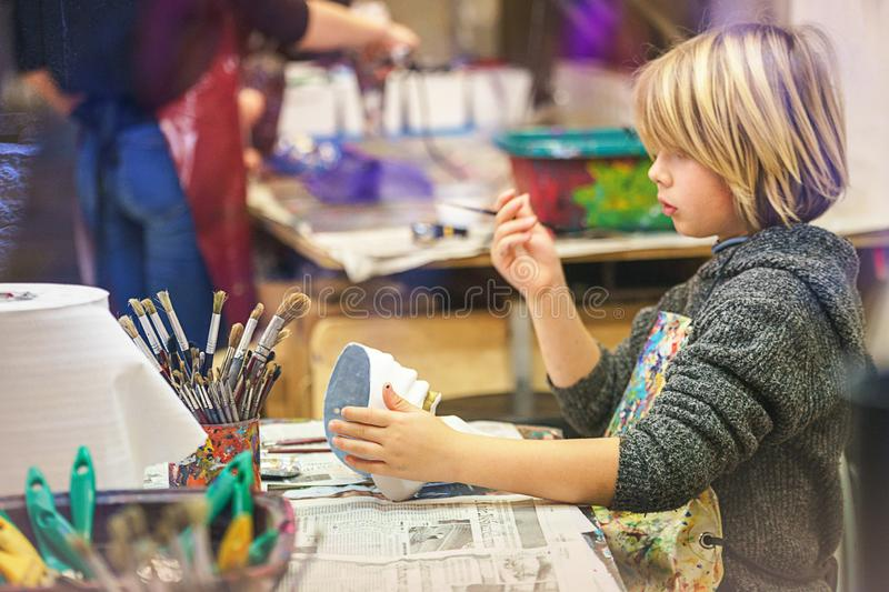 VENICE, ITALY - 02.23.2019: Happy face of little boy hands with venice tradition carnival mask, painting, making of mask during stock photo