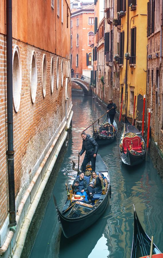 VENICE, ITALY - 02.23.2019: Happy faces of people in gondolas on Grand Canal during the carnival in Venice. Couple of young people stock photos
