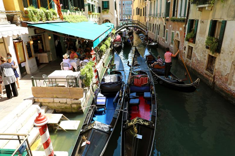 VENICE, ITALY - JULY 18, 2018: tourists on gondola in Venice channel, Italy stock photography