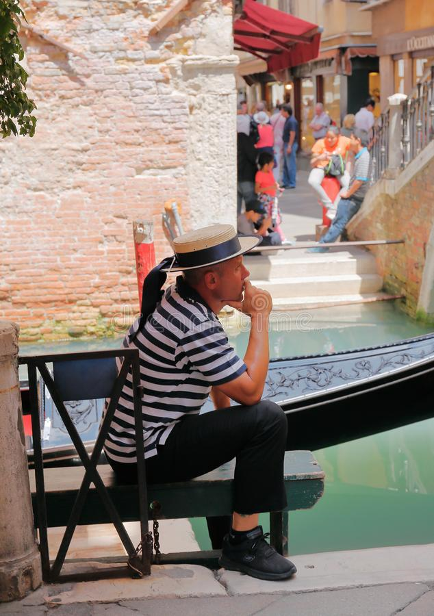 Gondolier on the pier. VENICE, ITALY. VENICE, ITALY - 26 JUNE, 2014: Gondolier on the pier. The profession of gondolier is controlled by a guild, which issues a stock image