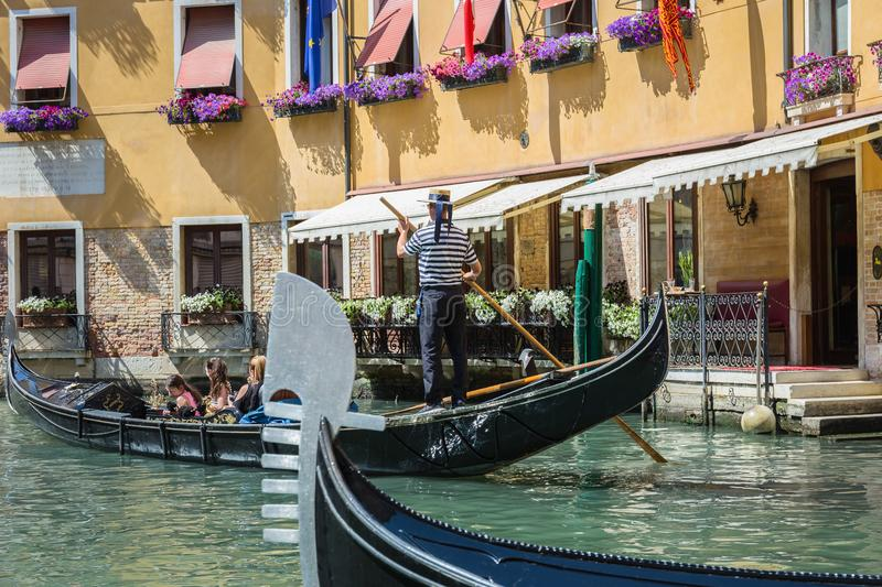 Gondolier rides gondola. VENICE, ITALY - 26 JUNE, 2014: Gondolier rides gondola. The profession of gondolier is controlled by a guild, which issues a limited stock photo