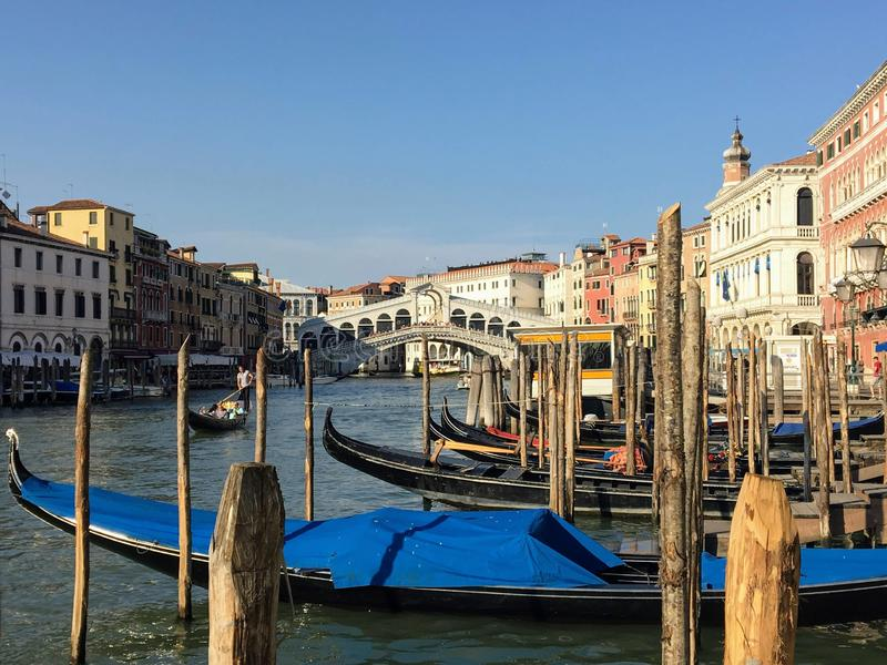 A classic view looking past wooden jetties and gondolas towards the Rialto Bridge in Venice, Italy along the Grand Canal on a beau royalty free stock photos