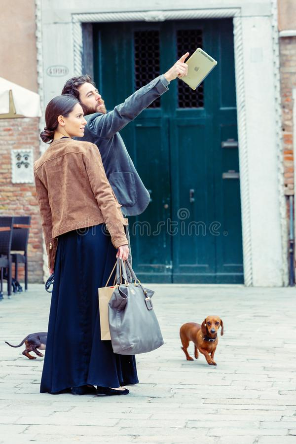 Beautiful thirties couple very well dressed with their dogs in a street. Venice, Italy - March 20, 2015:beautiful thirties couple very well dressed with their royalty free stock photos