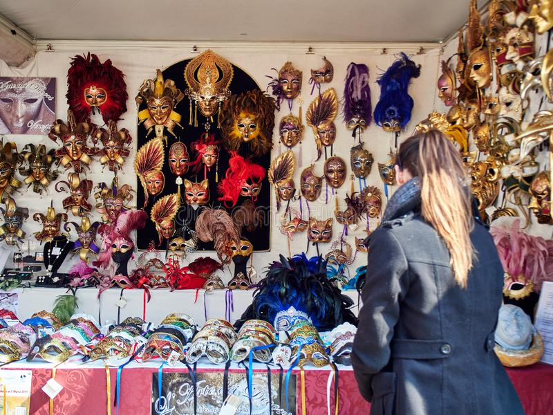 Venice, Italy - March 2, 2019 Tourist browse different mask models in a street market stand stock images