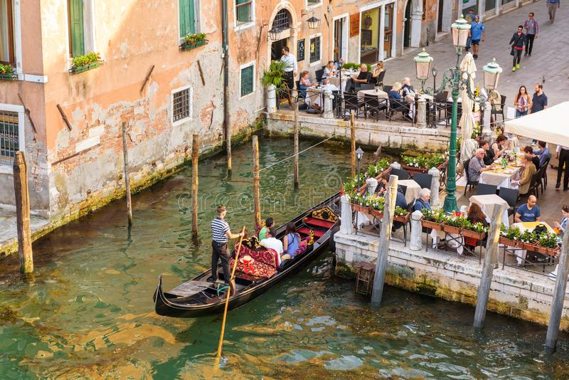 Gondola with people near street cafe in Venice, Italy stock image