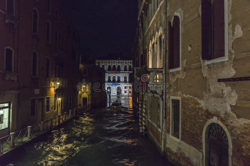 Venice in Italy at night. Small canal with grand canal in background in Venice at night , Italy , Europe royalty free stock image