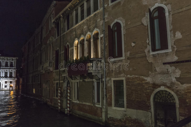 Venice in Italy at night. Small canal with grand canal in background in Venice at night , Italy , Europe royalty free stock photo
