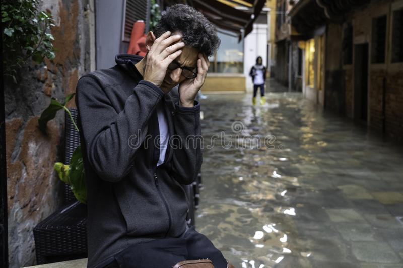 VENICE, ITALY -  November 17, 2017: flood acqua alta in Venice, Italy. Venice high water. waiter in the middle of high water. royalty free stock images