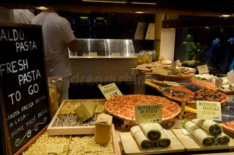 Italian Pizzaria Restaurant window display with vegetable rolls, pasta and pizza in Venice, Italy royalty free stock image