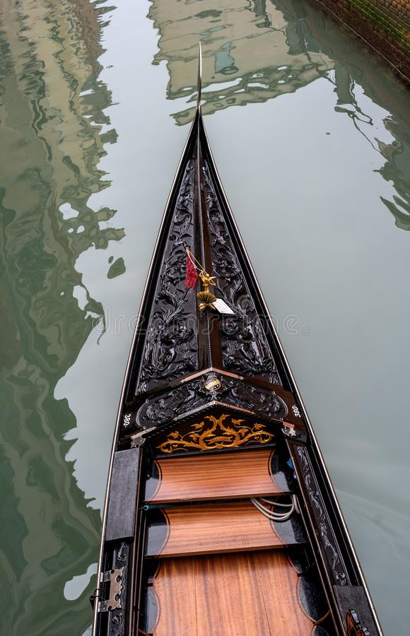Venice, Italy - October 13, 2017: The front part of the gondola from a height. The gondola is richly decorated with red royalty free stock images