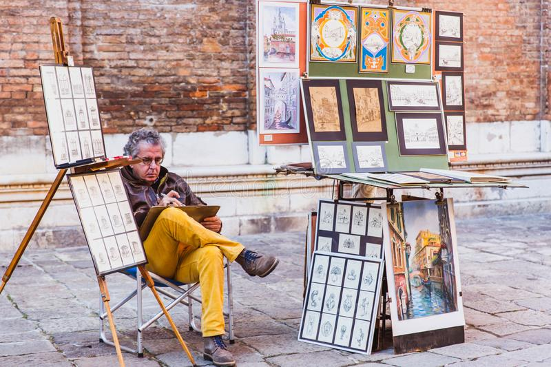 VENICE, ITALY - OCTOBER 27, 2016: A painter Painting canvas on street in Venice, Italy stock image