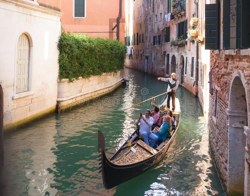 VENICE, ITALY - OCTOBER, 07 2017 Tourists travel on gondola on small canal royalty free stock image