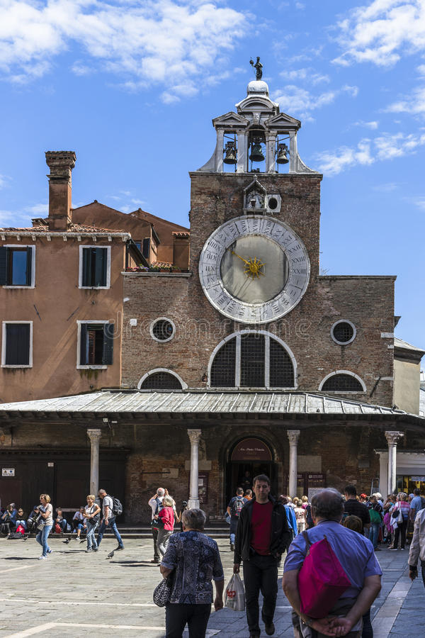 Venice in Italy. One of the many squares with tourists in Venice , Italy. Europe . Old church and tower with the clock royalty free stock image