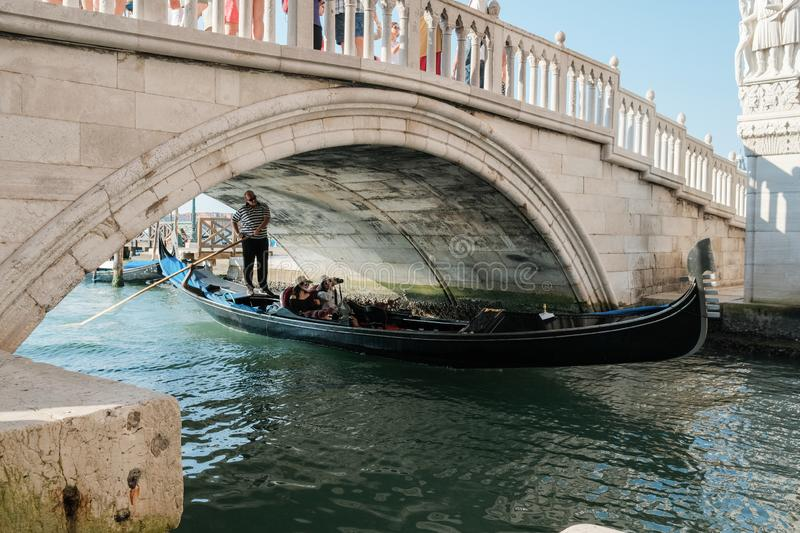 Gondolier rides tourists on a gondola under the bridge in Venice royalty free stock photography