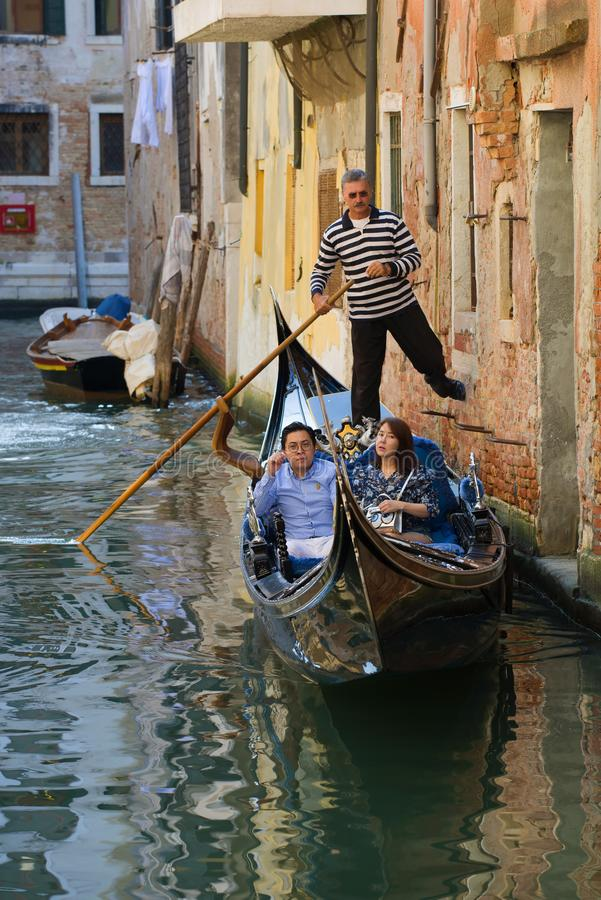 A pair of Asian tourists on a romantic trip in the gondola. Venice, Italy stock image