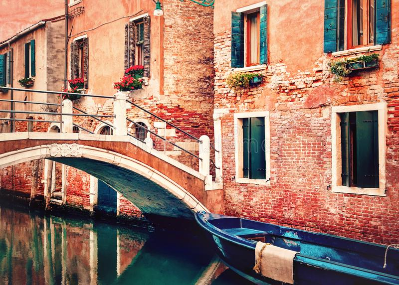 Venice, Italy. Small bridge over canal with blue boat and traditional orange historic buildings. Venice, Italy. Concrete bridge over canal with blue boat and stock images
