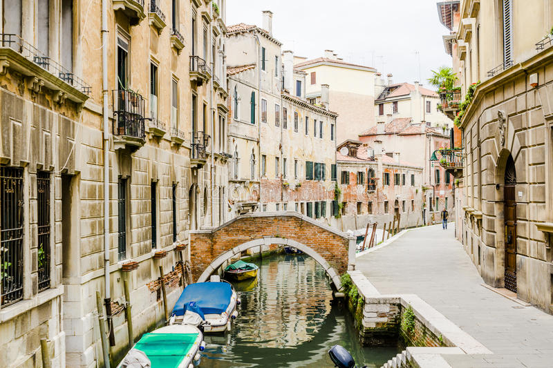 Venice in Italy. Small canal with boats people and bridge in Venice , Italy , Europe royalty free stock photos