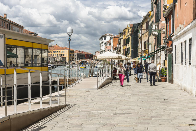 Venice in Italy. Small canal with the boats and people in Venice , Italy , Europe royalty free stock image