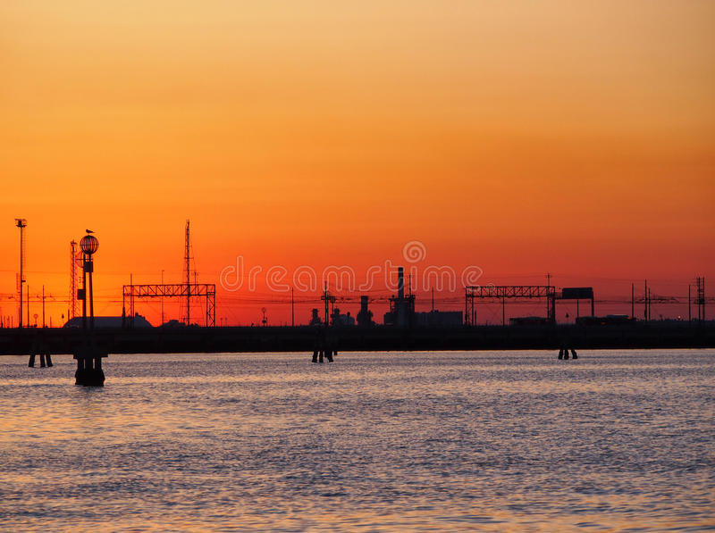 Venice lagoon with an orange sunset with the railway bridge royalty free stock photography