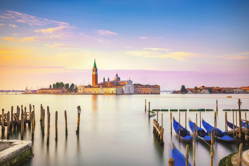 Venice lagoon, San Giorgio church, gondolas and poles. Italy stock photography
