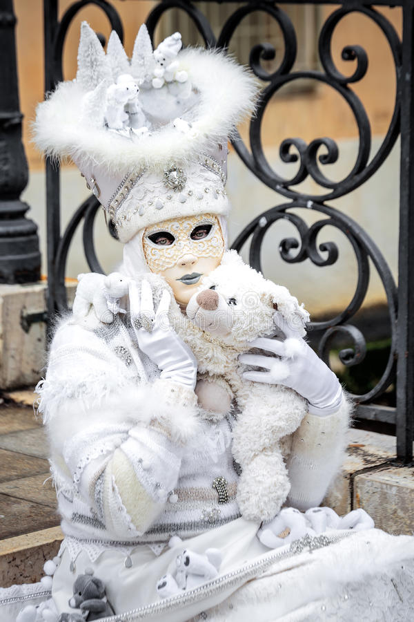 Venice mask with bear. Venice white carnaval mask sitting on stairs with toy bear,Italy stock images