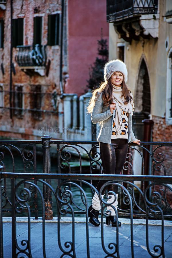 Tourist woman in Venice, Italy in winter looking into distance. Venice. Off the Beaten Path. Full length portrait of smiling modern tourist woman in fur hat in royalty free stock photo