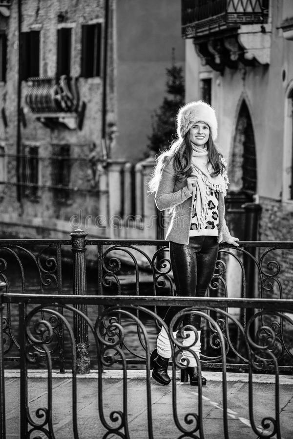 Tourist woman in Venice, Italy in winter looking into distance. Venice. Off the Beaten Path. Full length portrait of smiling modern tourist woman in fur hat in stock photo