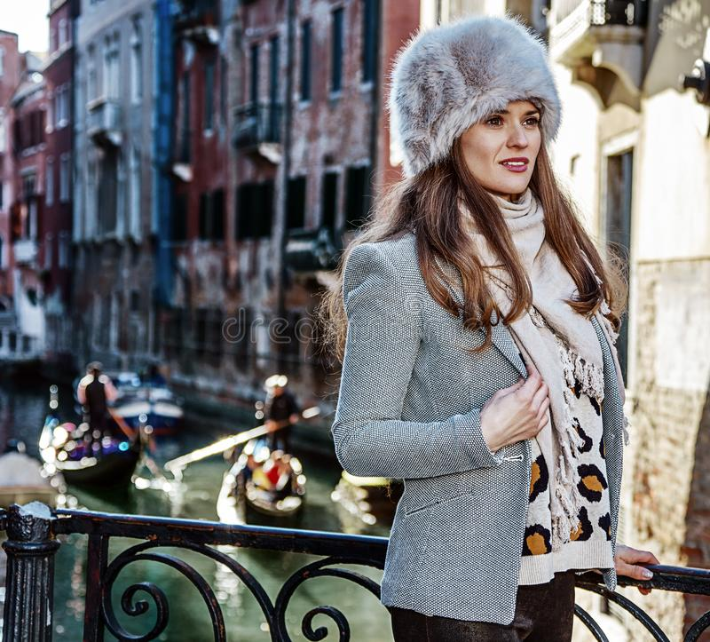 Tourist woman in Venice, Italy in winter looking into distance. Venice. Off the Beaten Path. modern tourist woman in fur hat in Venice, Italy in the winter stock image