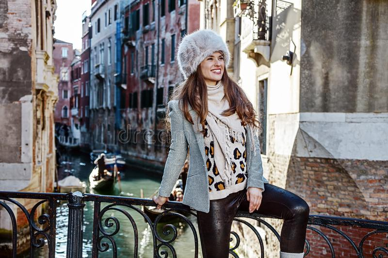 Smiling woman in Venice, Italy in winter looking into distance. Venice. Off the Beaten Path. smiling trendy woman in fur hat in Venice, Italy in the winter stock images