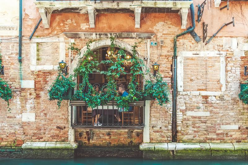 Venice September 4 2018: Beautiful view of the cafe windows, with tourists sitting in it, decorated with vertically growing plants stock photography