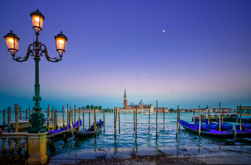 Venice, street lamp and gondolas or gondole on sunset and church on background. Italy stock photography