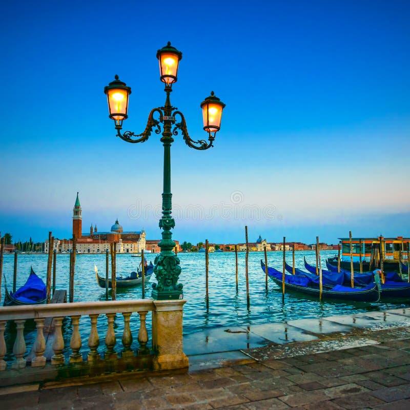 Venice, street lamp and gondolas on sunset. Italy. Venice, street lamp and gondolas or gondole on a blue sunset twilight and San Giorgio Maggiore church landmark royalty free stock photography