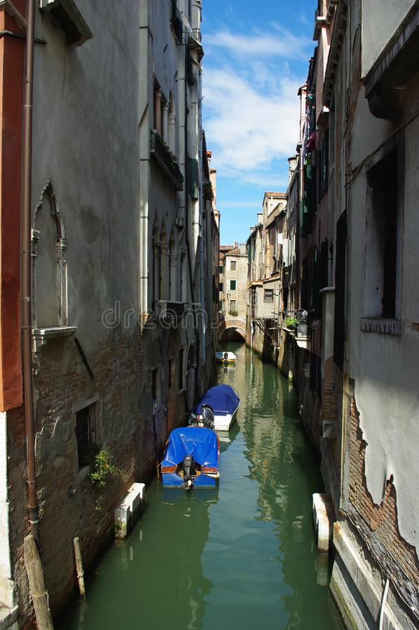 Venice. Three covered boats in a narrow Venetian canal. royalty free stock photography