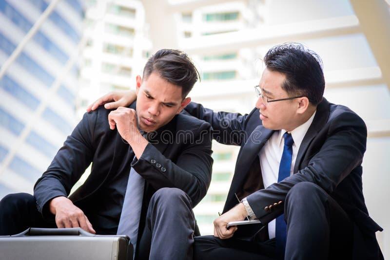 Venire a mancare triste e frustrato di tatto dell'uomo d'affari di due asiatici di ribaltamento nella vita immagini stock libere da diritti