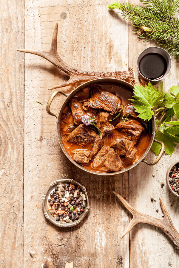Venison Goulash in Pot on Wooden Surface royalty free stock photo