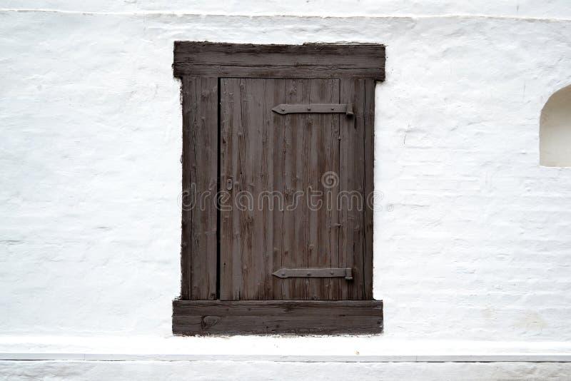 Venster in de gepleisterde muur van oude houten gesloten blinden royalty-vrije stock foto