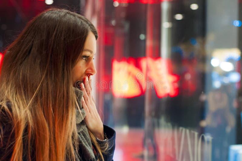 Venster die, vrouw die de opslag bekijken winkelen Glimlachende vrouw die op het winkelvenster richten alvorens stor in te gaan stock foto