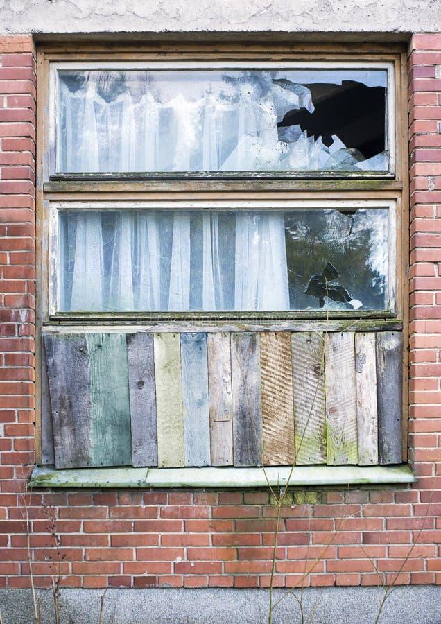 Venster door houten panelen in een oud rood baksteenhuis dat omhoog wordt ingescheept royalty-vrije stock fotografie