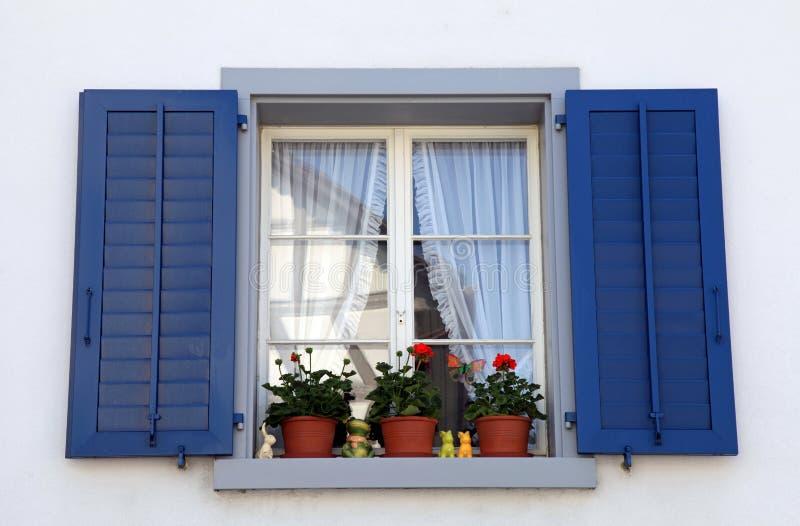 Venster met blauwe blinden en bloempotten, Zwitserland. stock afbeeldingen