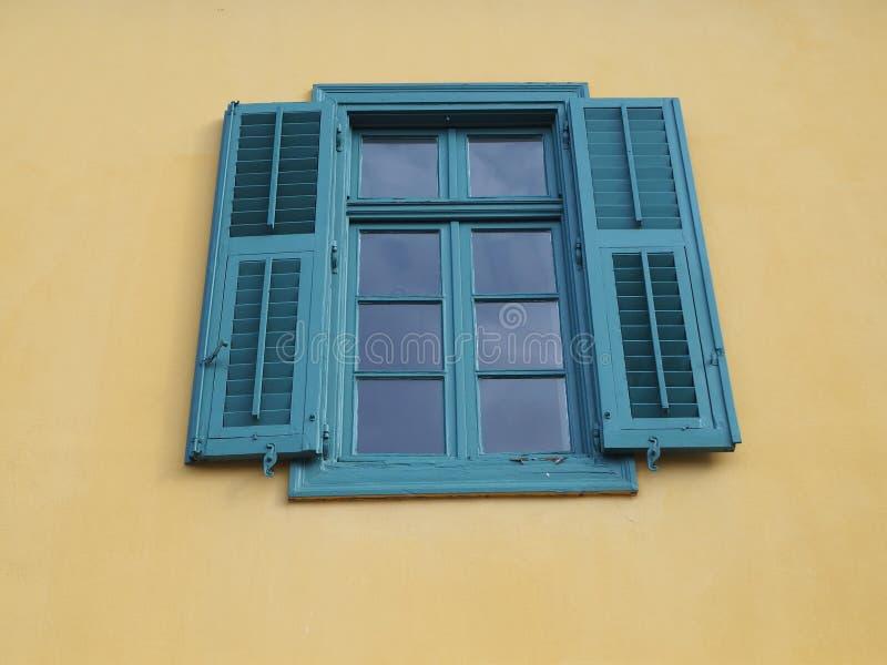 Venster met blauwe of groene blinden op een gele muur stock afbeeldingen