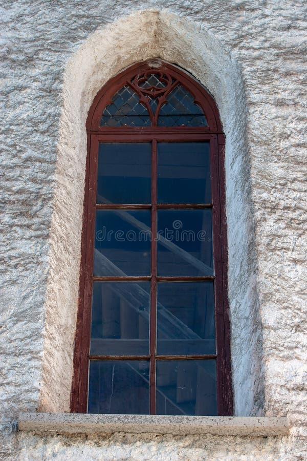 Venster met een rood houten kader bij de oude kerk stock foto