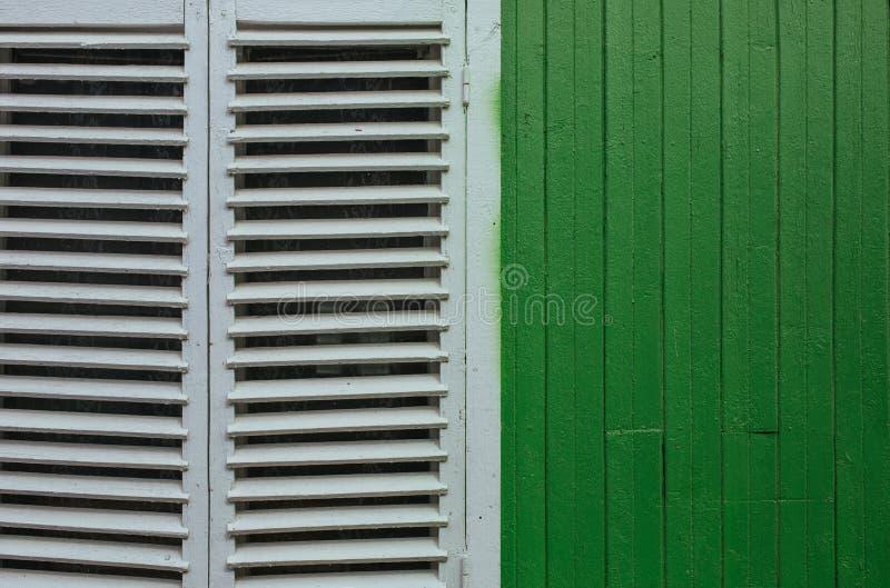 Venster met gesloten witte jaloezie op groene muur royalty-vrije stock afbeelding