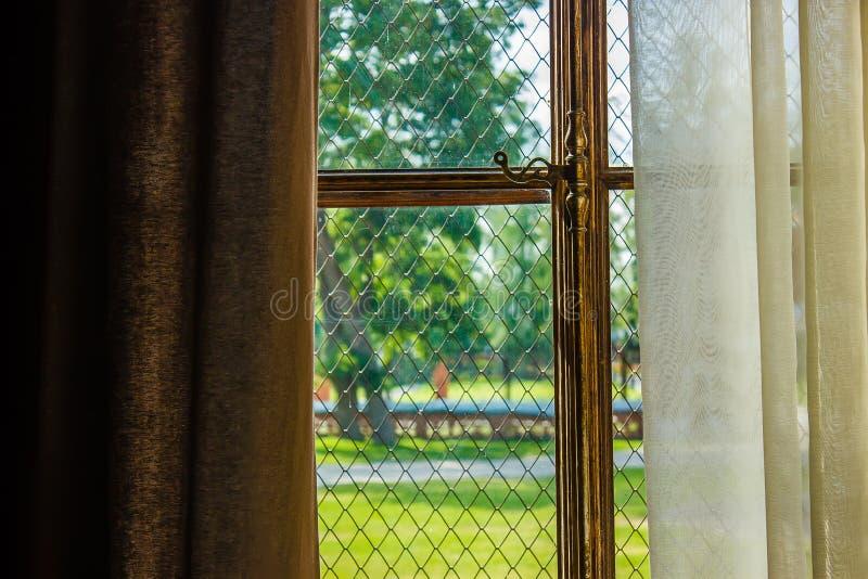 Venster met gordijnen met verguld raamkozijn, luxe vi wordt behandeld die stock foto