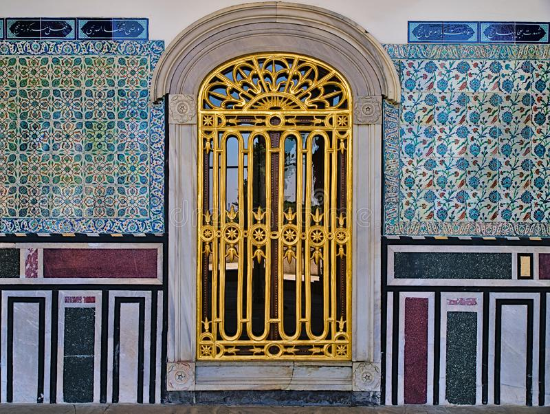 Venster met gouden traliewerk en klassiek oosters ontwerp op betegelde muur stock foto's