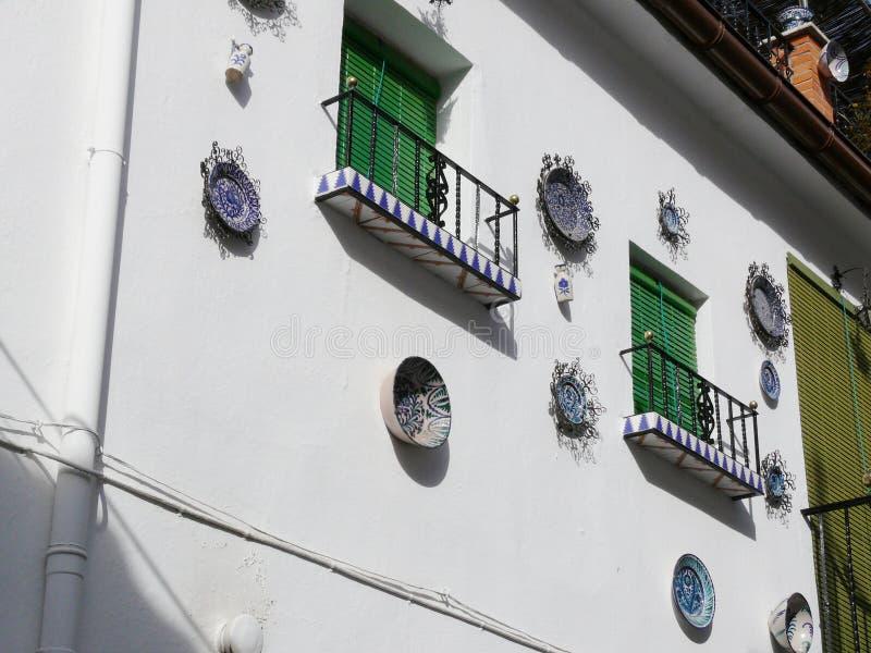 Venster met sunblindgordijn en voorgevel met ceramische decoratie stock foto