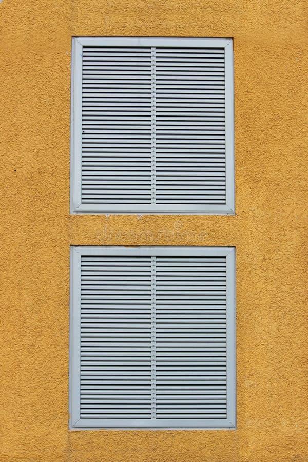 Venster twee in een groot industrieel winkelcentrum sloot met externe jaloezie in de vorm van ventilatietraliewerk geeloranje B royalty-vrije stock foto's