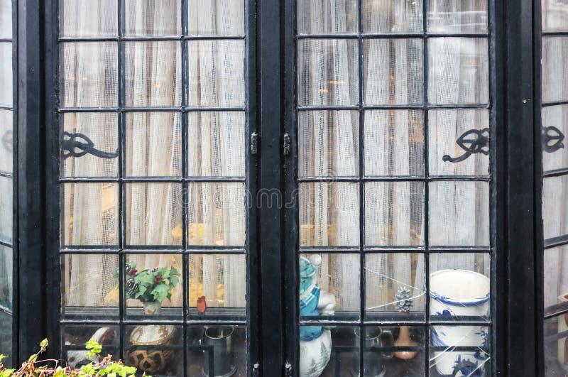 Venster van bescheiden huiselijk huis - gebroken zwarte metaalerker met netto gordijnen en knick-knacks die binnen zitten stock foto's