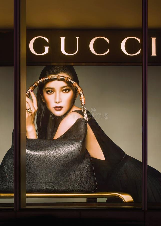 Venster van een Gucci-afzet met beeld bij nacht stock fotografie