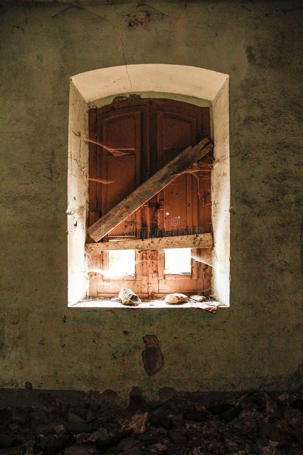 Venster van een verlaten van binnenuit genomen huis; het licht verlicht de ruimte een weinig, verlatend een glimp van de spinnewe royalty-vrije stock fotografie